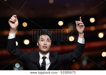Young conductor with baton raised at performance