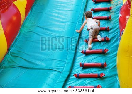 Little Boy Playing On An Inflatable Playground