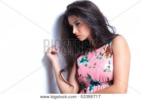 side view of a sad woman looking down and leaning a white wall