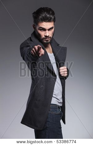 serious man with long beard in a coat is pointing his finger accusing you