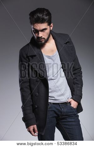 young bearded man in long coat is posing with one hand in his pocket