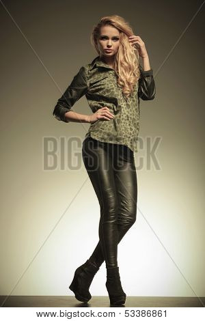 young fashion blonde woman in leather pants posing and looking away from the camera
