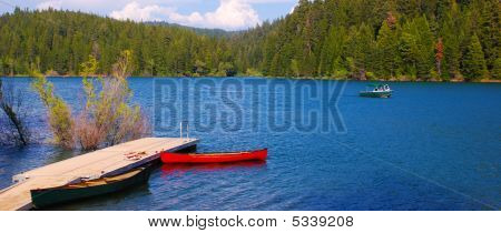 Canoes And Speedboat On A Lake