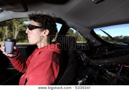 Man Driving and Drinking Coffe
