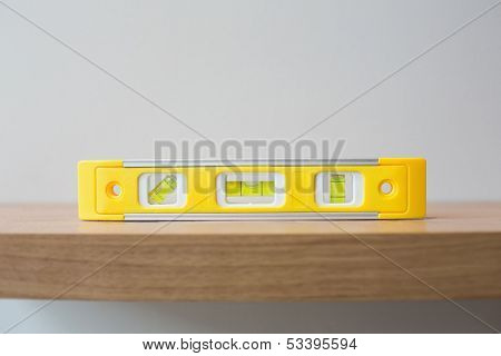 Close up of a spirit level on wooden surface against the wall