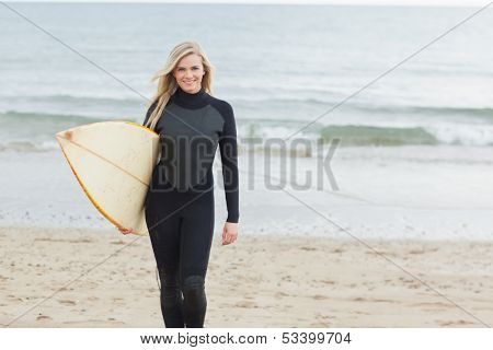 Portrait of a smiling young woman in wet suit holding surfboard at beach