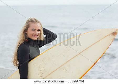 Portrait of a beautiful young woman in wet suit holding surfboard at the beach