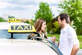 Young woman and driver standing together in front of taxi, she has reached her destination poster