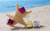 stock photo of starfish  - Starfish with few Christmas gift box on the sandy beach by the ocean - JPG