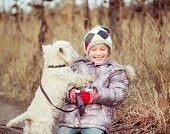 foto of westie  - little cute girl with her dog breed White Terrier  in a field in autumn - JPG