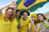 foto of enthusiastic  - Group of happy Brazilian soccer fans commemorating victory - JPG
