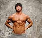 picture of beanie hat  - Handsome man with muscular torso in beanie hat posing - JPG