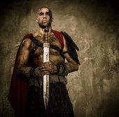 stock photo of legion  - Wounded gladiator holding sword covered in blood with both hands - JPG