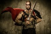 pic of legion  - Wounded gladiator in waving coat holding sword covered in blood - JPG