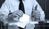 stock photo of politician  - Hand putting a blank ballot inside the box elections concept BLUE TONE - JPG