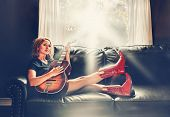 stock photo of cowgirl  - a cowgirl playing the guitar on a couch - JPG