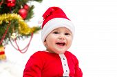 foto of santa baby  - Happy smiling baby wearing a red and white Christmas Santa hat and suit isolated on a white background - JPG