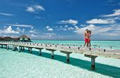 stock photo of jetties  - Couple on a tropical beach jetty at Maldives - JPG
