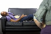 stock photo of couch potato  - young lazy male sleeping on the couch and making a mess - JPG