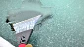 stock photo of ice-scraper  - scraping snow and ice from the car windscreen - JPG