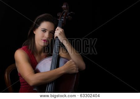 Beautiful Brunette Holding Cello With Selective Light In Red Dress