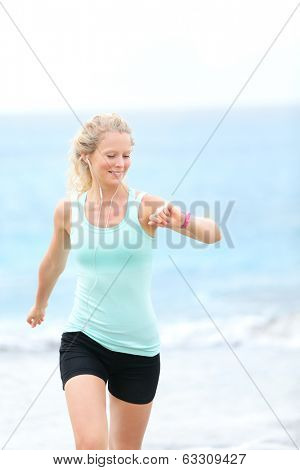 Running woman jogger looking at heart rate monitor watch outside jogging on beach. Female fitness runner girl jogger training listening to music in earphones. Beautiful young blonde woman in her 20s.