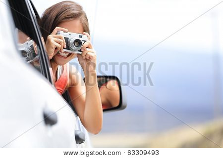 Woman tourist taking photo in car with camera driving on road trip travel vacation. Girl passenger taking picture out of window with vintage retro camera.