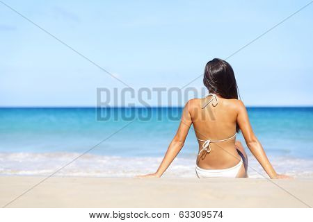 Woman on beach sitting in sand looking at ocean enjoying sun and summer travel holidays vacation getaway. Girl in bikini relaxing under blue sky.