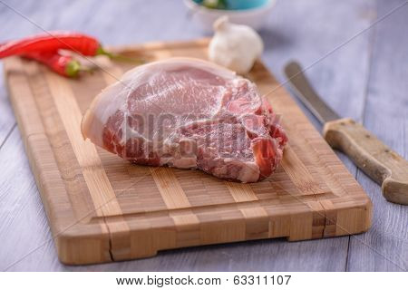 Raw Pork Chops On The Cutting Board With Some Chili And Garlic