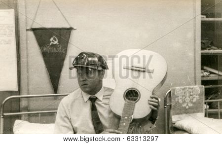 Vintage photo of man in hard hat holding a guitar (in Russia, 1970's)