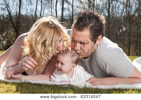 Young Parents Are Kissing The Baby