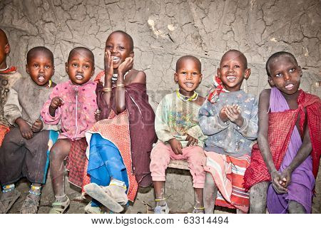 AFRICA, TANZANIA-FEBRUARY 9, 2014: Portrait on unidentified African Kids of Masai  tribe village smiling to the camera,  living in house made with cow dung , February 9, 2014. Tanzania.
