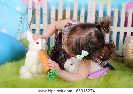Sweet Toddler Girl Feeding Bunny At Easter