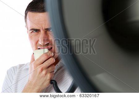 Closeup portrait of a man roaring loudly into megaphone