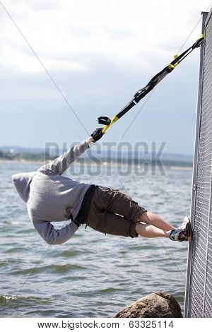 hooded man outdoor,suspension training at the sea - back view