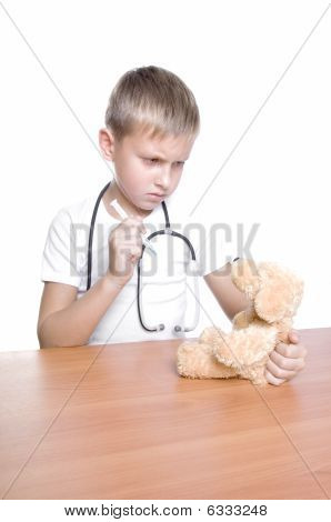 Cute Young Boy Playing Doctor With His Stuffed Bear And Syringe