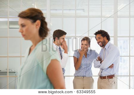 Colleagues gossiping with sad young businesswoman in foreground at a bright office