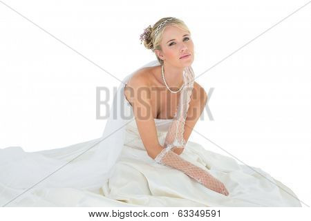 Portrait of sensuous woman in wedding dress sitting over white background