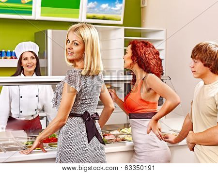 Women at cafeteria buying food.