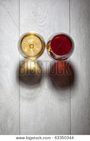 Glasses of red and white wine on wooden table. Top view