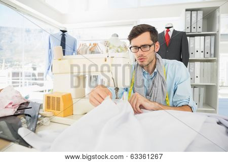 Concentrated young male tailor sewing in workshop