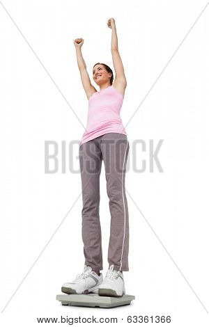 Low angle view of a young woman cheering on weight scale over white background
