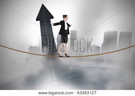 Businesswoman performing a balancing act against road turning into arrow
