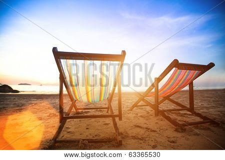 Vacation concept, pair of beach loungers on the deserted coast sea at sunrise.