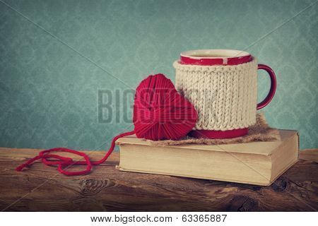 Cup of coffee standing on an old book and wool heart