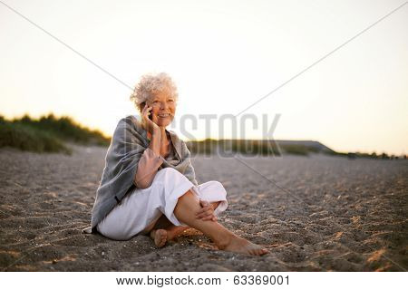 Retired Woman In The Beach Making Phone Call