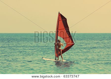 windsurfer girl on blue sea - vintage retro style