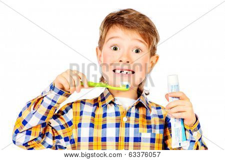 Little funny boy smiling and brushing his teeth. Healthcare. Isolated over white.