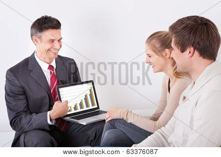 Advisor Showing Graph On Laptop To Couple