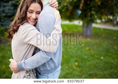 Happy girl embracing her boyfriend in park